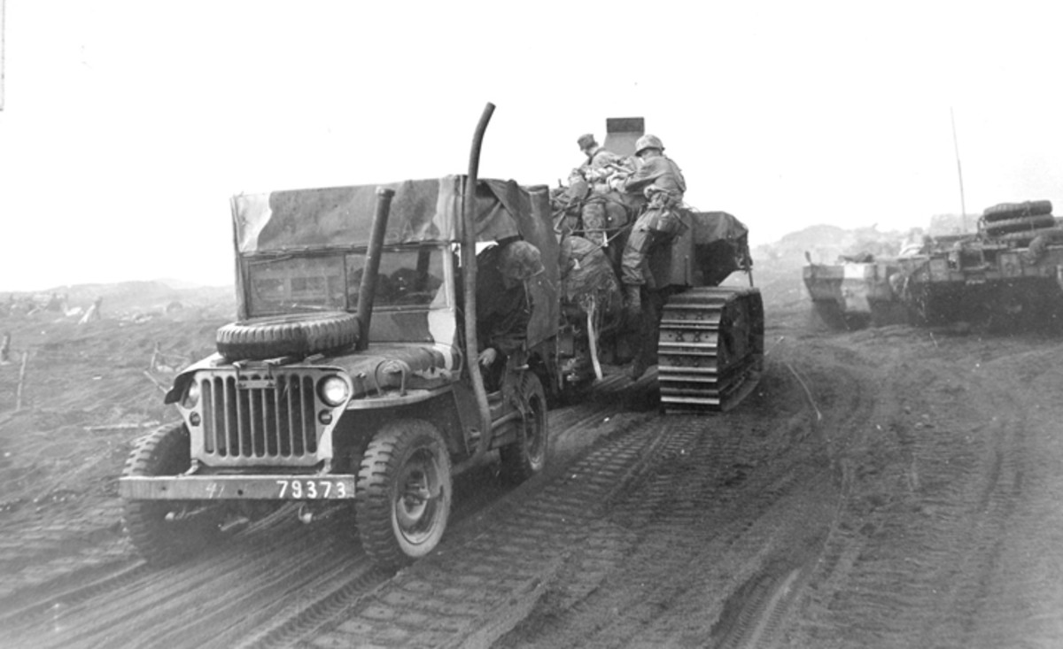 This camouflaged Holden Jeep is being towed backwards by an International TD-14 on Iwo Jima. Of special interest is the air intake extending through the hood and the continuation of camo onto the canvas.