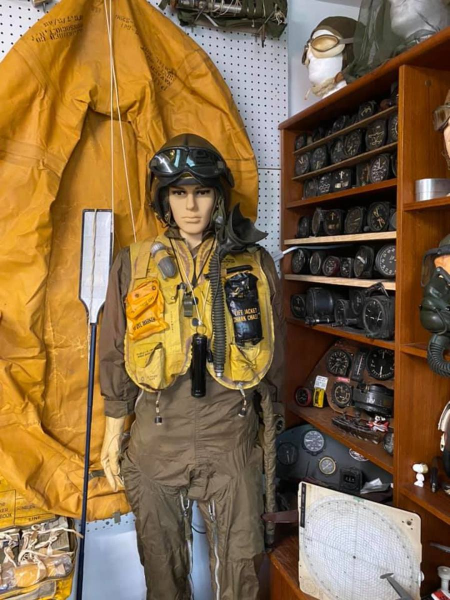 Mannequin dressed in pilot gear with lifeboat behind him.