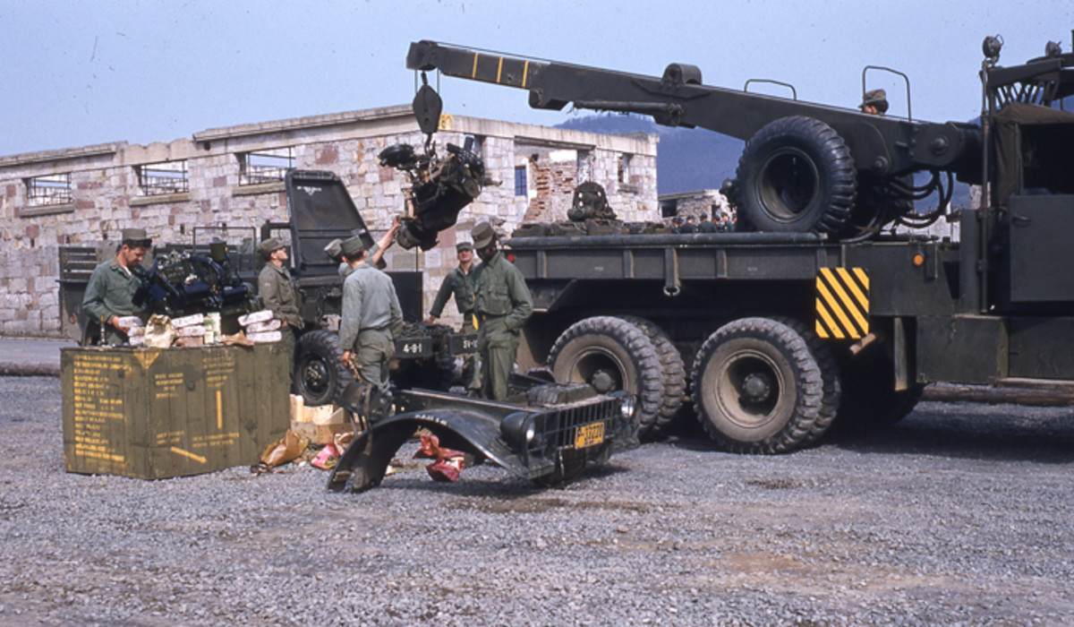 An M62 assisted in an engine swap on an M37 Dodge 3/4-ton truck. The first mass-produced M-series five ton wrecker, the M62, can be distinguished from the later M543 (with which it shared a chassis) by the spare tire mounted on the shipper.