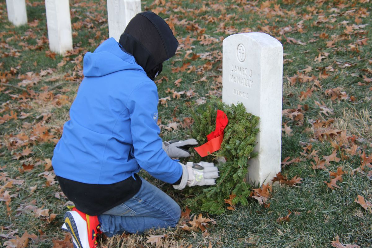 Boy places wreath at government-supplied tombstone.