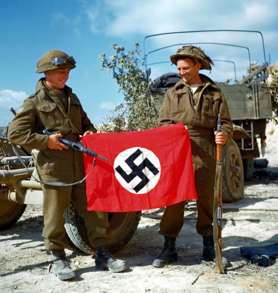 Canadian troops posing with a captured German flag, near Hautmesnil, France, 10 Aug 1944; note Sten gun and Lee-Enfield rifle .
