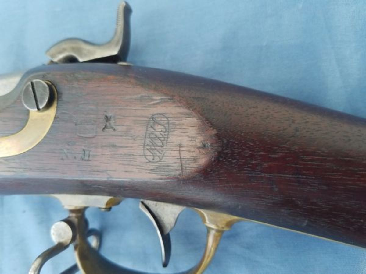 """Some of the New Hampshire alteration Model 1841s are surcharged """"N.H."""" in the wood stock opposite the lock plate."""