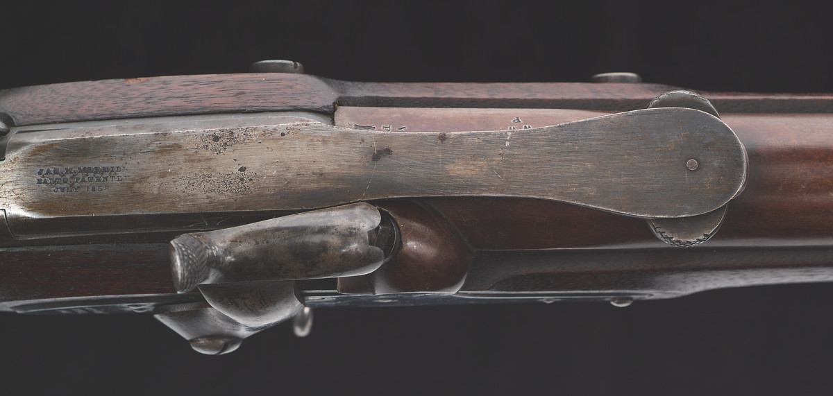 This device incorporated a lever which, when raised, opened a chamber where the cartridge could be inserted. Lowering the lever activated a breech plunger that seated cartridge into the breech. The lever bears the three-line Merrill marking: JAS. H. MERRILL / BALTO PATENTED / JULY 1858.