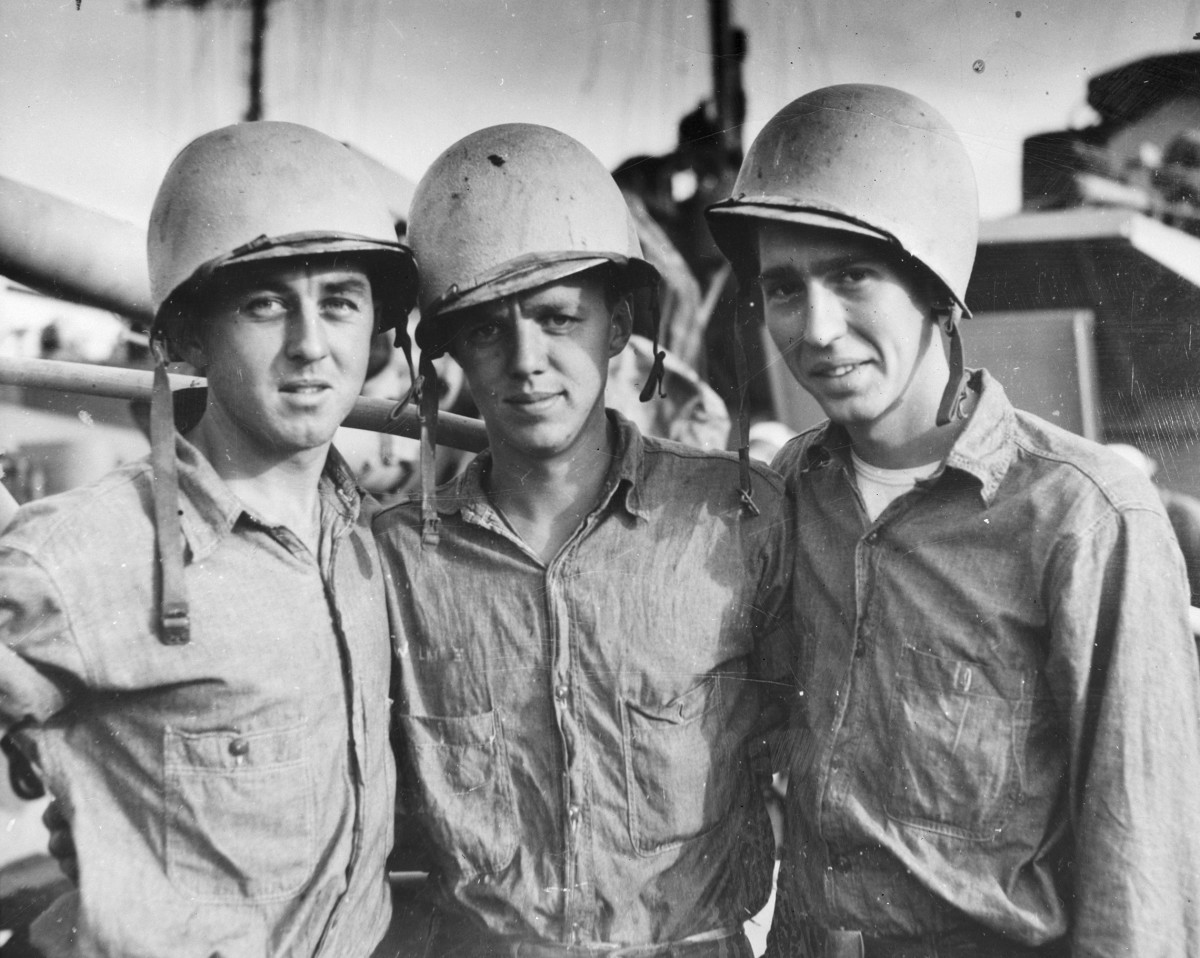 Sailors in the United States Coast Guard are shown posing for a photograph. Pictured left to right, are Thomas L. Crone, Machinist's Mate Third Class, John A. Wilhite, Seaman First Class, and Raymond L. Wallace, Seaman First Class.