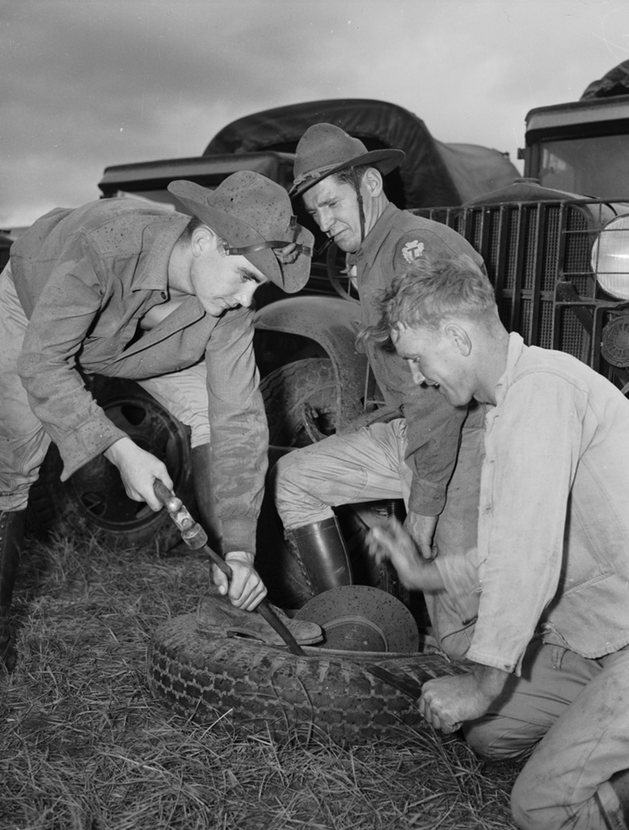 Texas National Guard maneuvers in Louisiana. Changing a tire is no different in the army from anywhere else. It's hard work unless you are a graduate of an automobile service station. Shown as they wrestle with a recalcitrant front tire of a big army truck are, left to right Private Jack Morrow, Sergeant T. M. Newman and Private John Powers, all of First Battalion, Headquarters Battery, 131st Field Artillery.