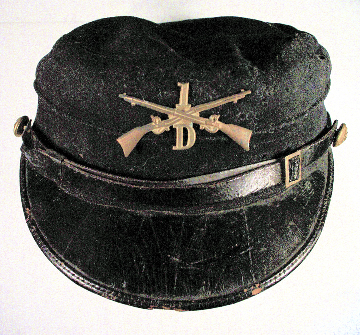 Model 1895 kepi originally worn Infantry Private Bert M. Bartlett, a railroad worker from Devils Lake, North Dakota. The solid brass branch insignia with a screw-post fastener on the reverse replaced the Pattern 1872 branch insignia in 1896.