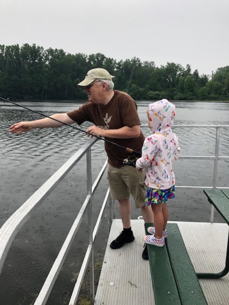 JAG helping granddaughter fish.