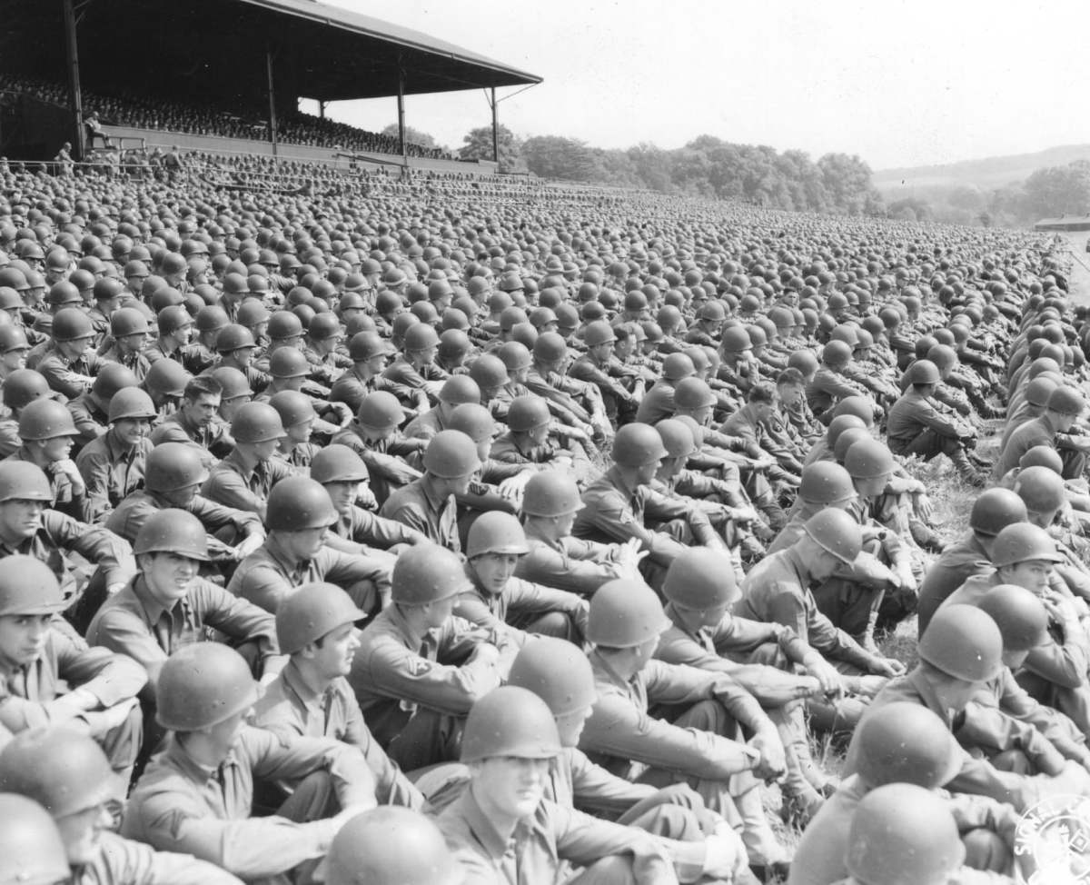Taken in May 1944, in Cambridge, England, thousands of American soldiers attending a Memorial Day service wearing their helmet liners.
