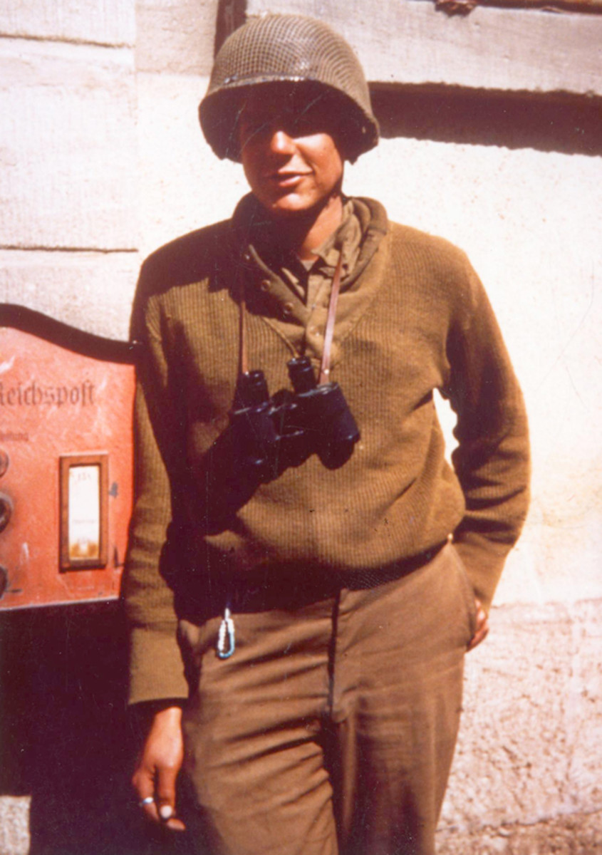 Ed Goeppinger posing in front of German building on his 20th birthday on April 19, 1945, wearing his steel M1 helmet with net covering.