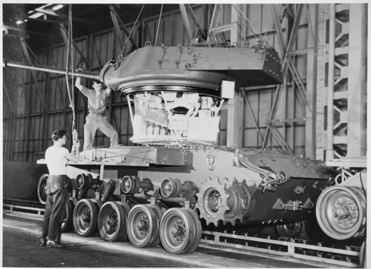 A complete early turret assembly is lowered into a Walker Bulldog chassis. The weld seam visible near the base of the turret aligns with the bottom of the  turret bustle. On later  production turrets this seam is much lower on the turret.