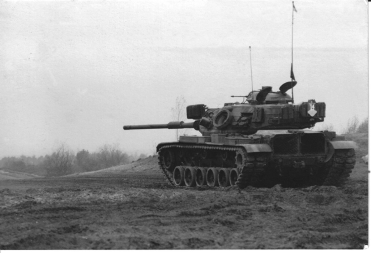 "Dan Wolverton was in Charlie Co. 2/66 Armour, 2nd Armored Division Forward. The M60A1 Rise Passive had smoke grenade launchers. This was the second tank Dan was on with the bumper number ""C-14"". The first one was transferred from 1st Platoon to the 2nd and he got this one as a replacement from 2nd platoon. The original C-14 didn't have smoke launchers. The photo was taken on tank Table 8, at Bergen Hohen Near (Bergen Belsen) Germany in 1981. The DI on the bussel rack is made of plywood with the company letter and vehicle number painted on it."