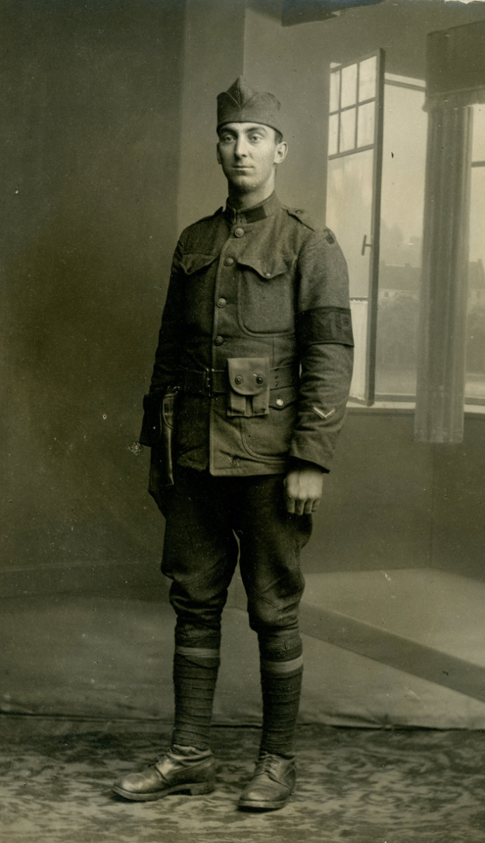 Unidentified 90th Division military policeman posing in the same studio featuring the open-window painted backdrop. The handle on the left window and the heavy drapery between the two windows are indicators of the backdrop used in the Loos studio.