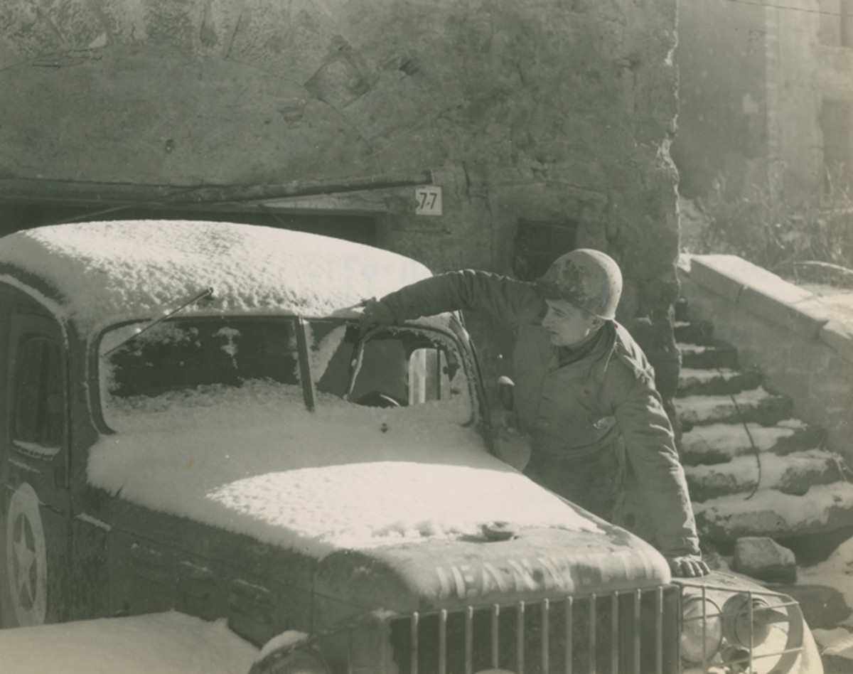 T/5 Anthony J. Sedivy,y wiping the snow from the windshield of an Army vehicle called 'Jeannette.' '9 Nov 44. 5/MM-44-6710. Fifth Army, Monghidoro, Italy. Sedivy was a member of the 791st Ordnance Co. Signal Corps photo