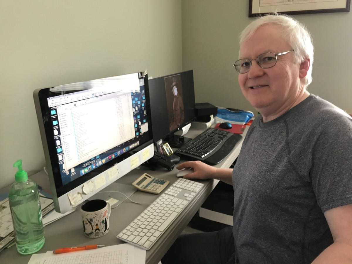 Photo of John Adams-Graf in temporary office space with hand sanitizer, two computers, and a pistol on his desk.