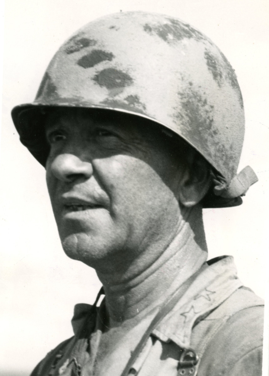 96th Division General JL Bradley wearing a camouflage-painted M1 helmet.