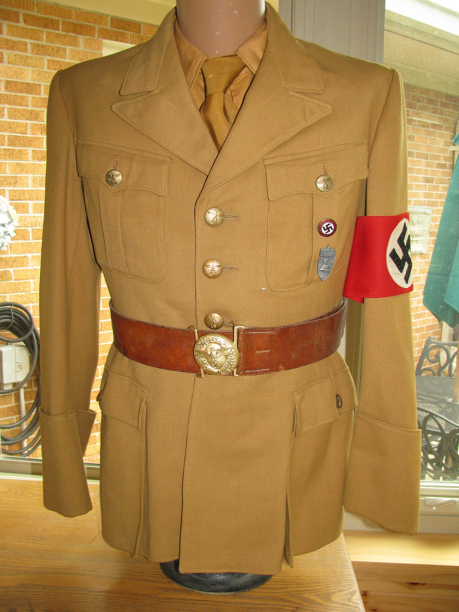 An Ortsgruppe tunic as worn by a low level official with party pin, regular party armband, belt buckle and Nuremburg pin.