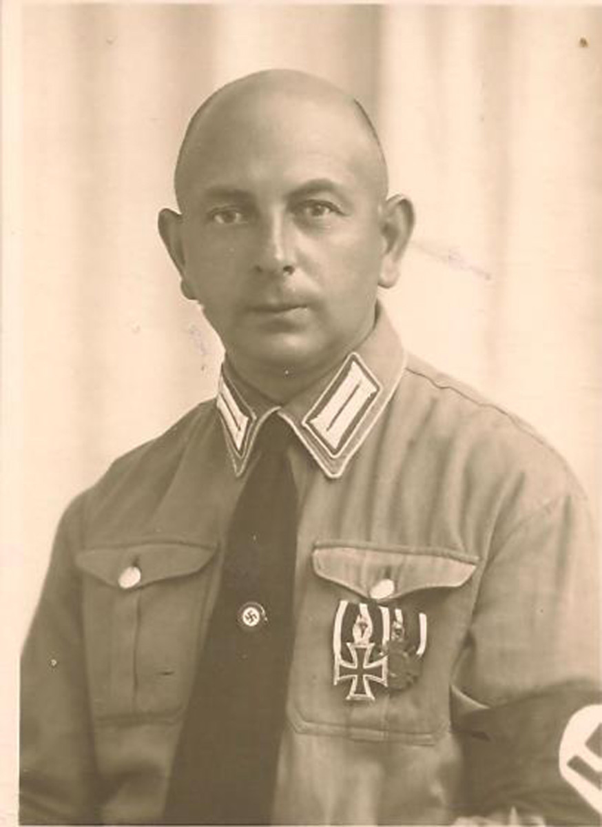 This early political leader was a WWI combatant who was awarded the 2nd Class Iron Cross and Hindenburg Combatant's Medal. He wears the standard brown shirt, armband, and NSDAP membership pin on his tie.