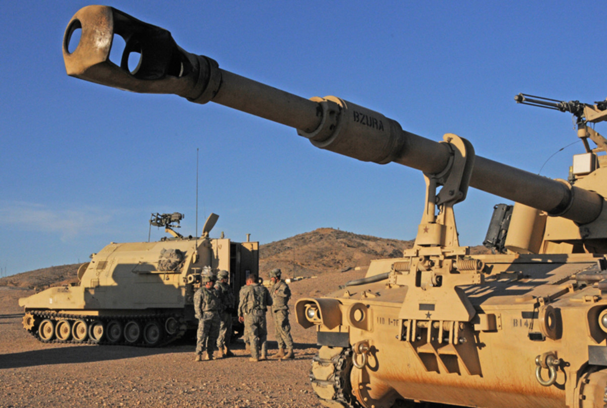 'Soldiers stand in front of an M923 Field Artillery Ammunition Support Vehicle that hauls ammunition for the M-109A6 Paladin, in the foreground.