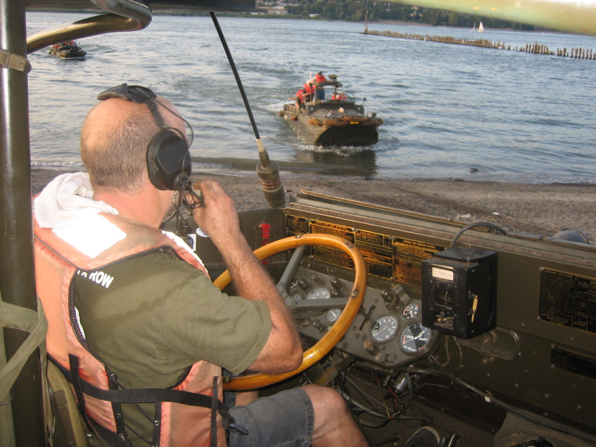 View over the shoulder of a DUKW pilot looking out at another amphibious vehicle in the water.