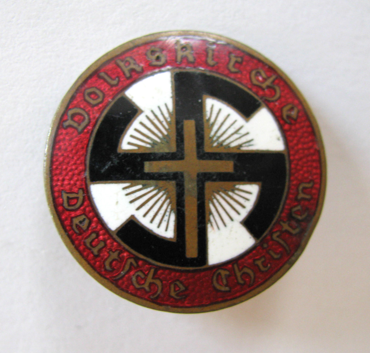 "Another example of the Deutsche Christen membership pin has an additional word at the top: ""Volkskirche"" (people's church)."