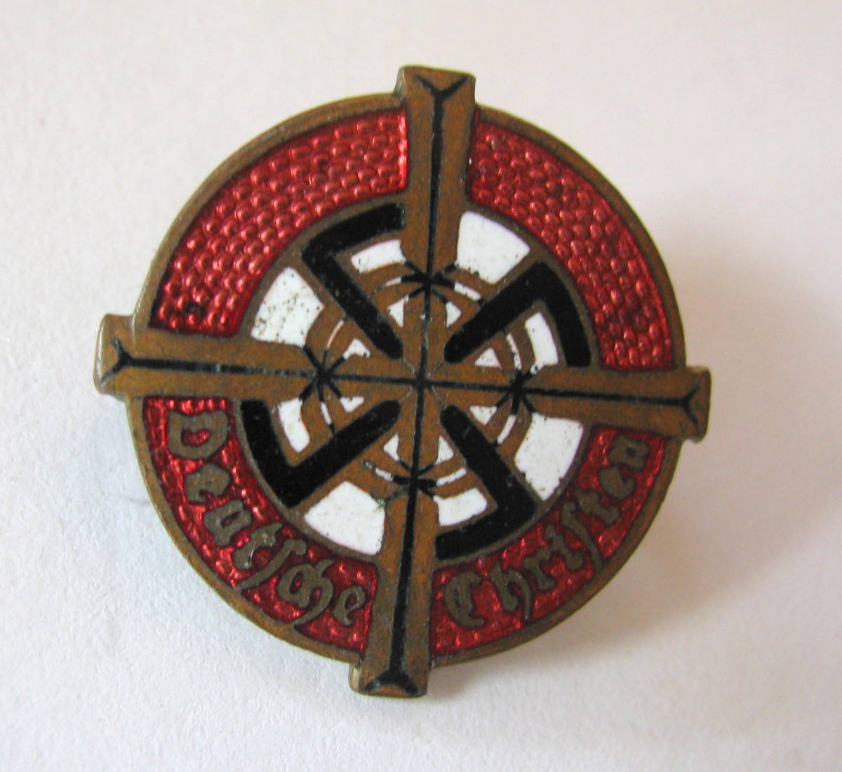 An example of the Deutsche Christen enamel membership pin carried the name of the group with a richly decorated golden cross on red and white field.
