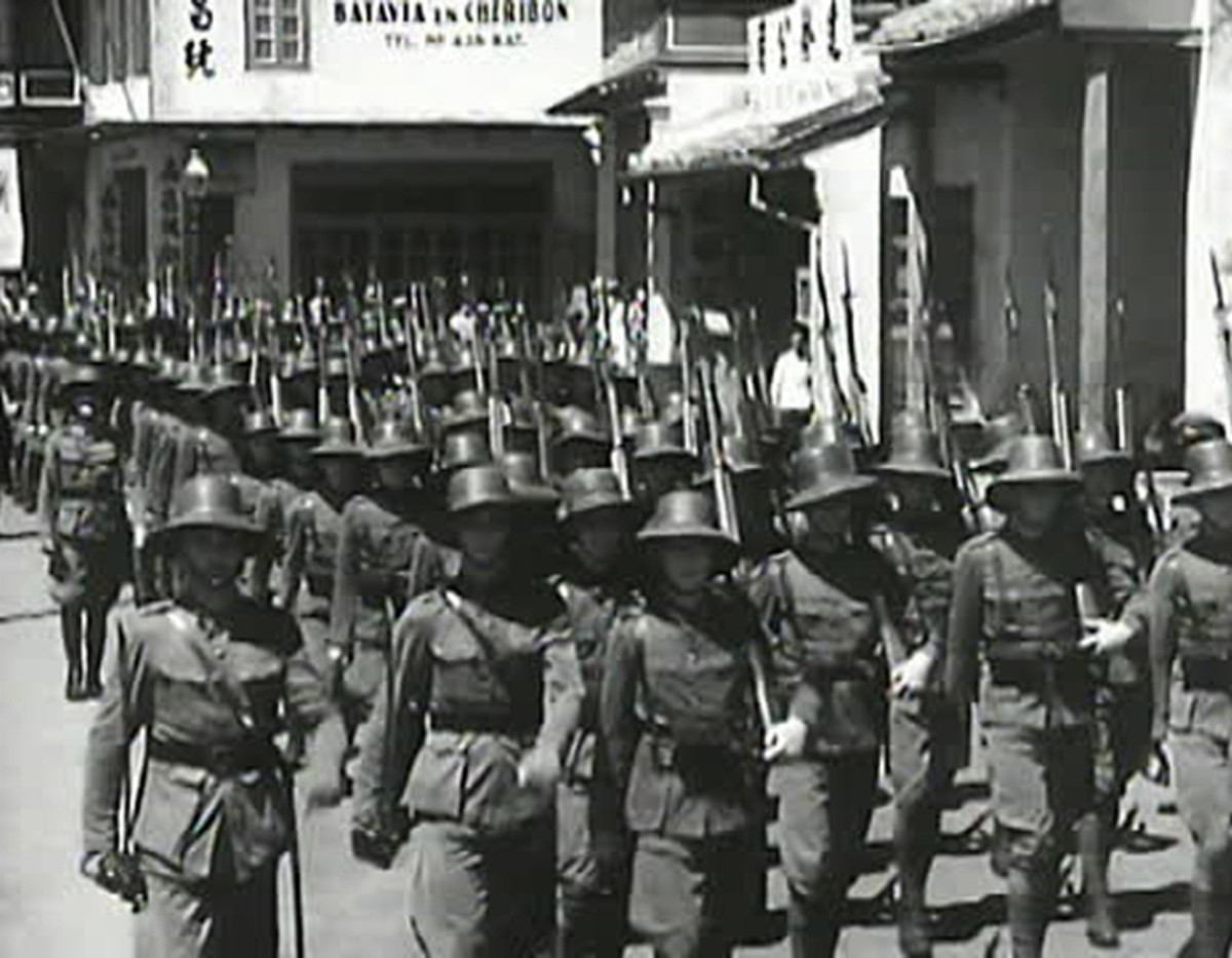 "A still image from a period newsreel shows KNIL troops in 1940 wearing the  ""bamboo"" hat that was issued due to shortages of the steel helmet."