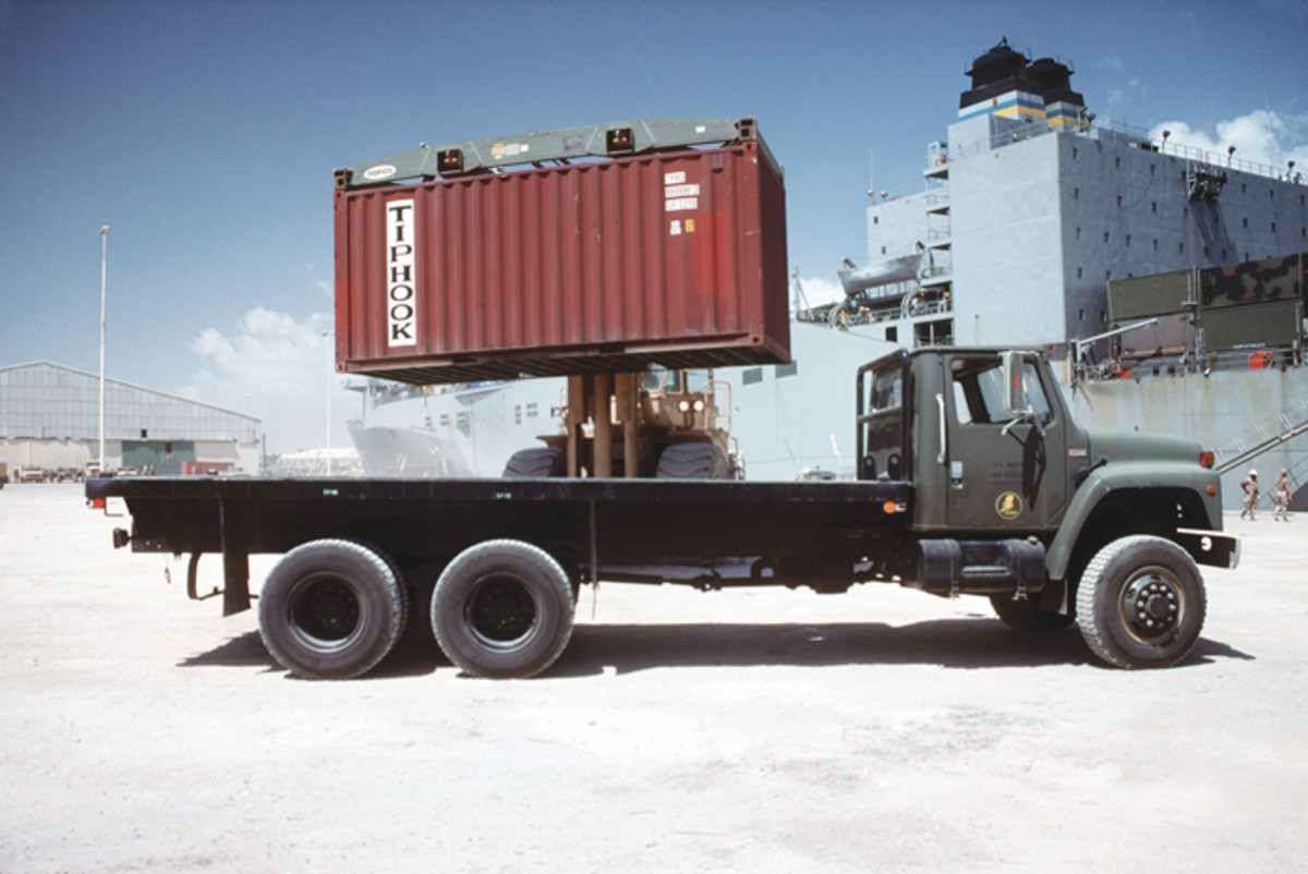 A container, unloaded from the Algol class vehicle cargo ship in the background, is lowered onto a gray-painted Seabee flatbed truck during the multinational relief effort, Operation Restore Hope.