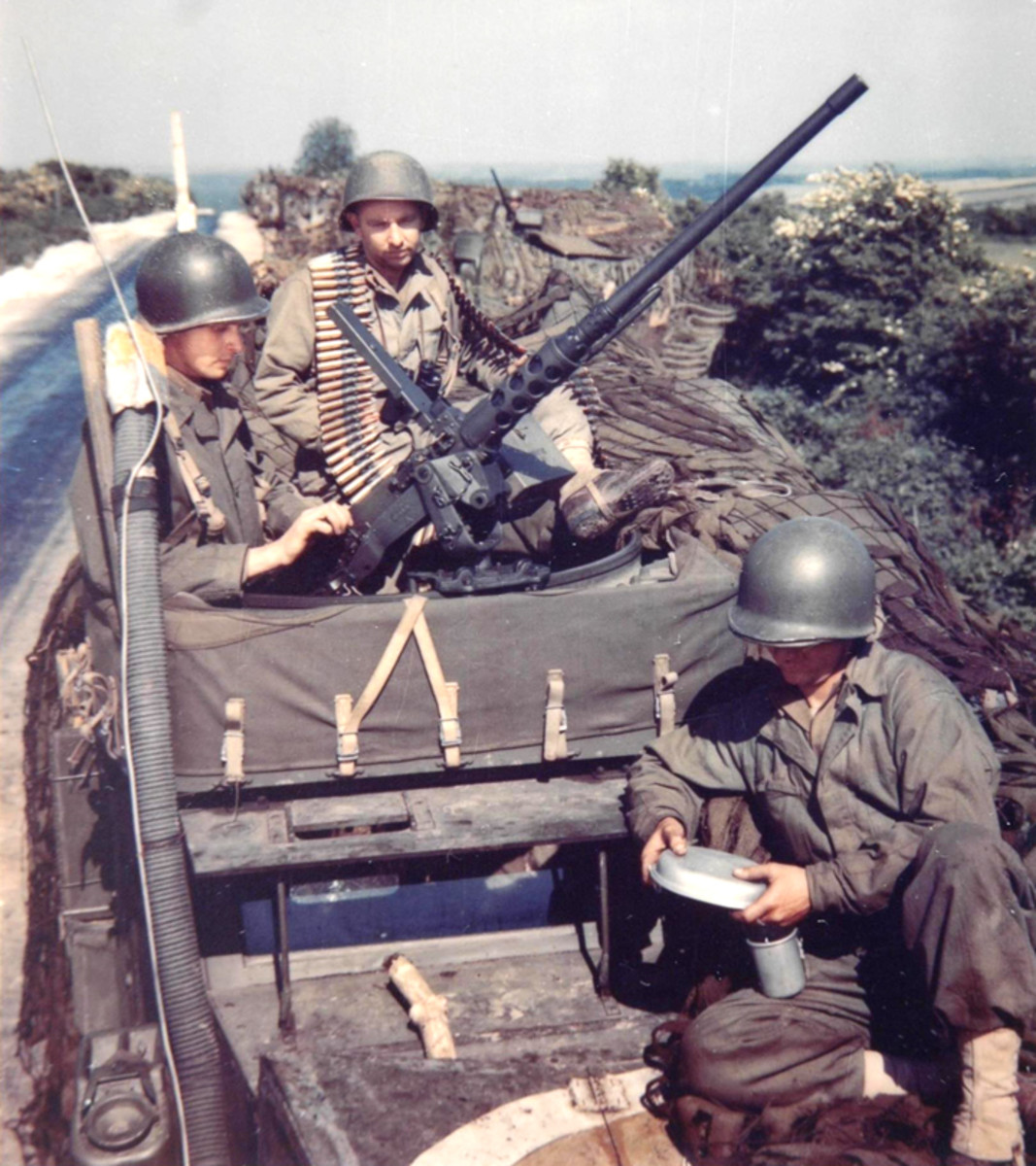 WWII color image of soldiers photographed in England. They are making final checks to the M2 machine gun mounted on their half-track.