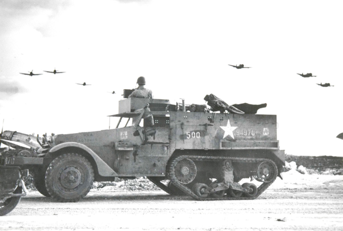 The crew of this M2A1 stands watch as a flight of P47 Thunderbolts pass over their base.