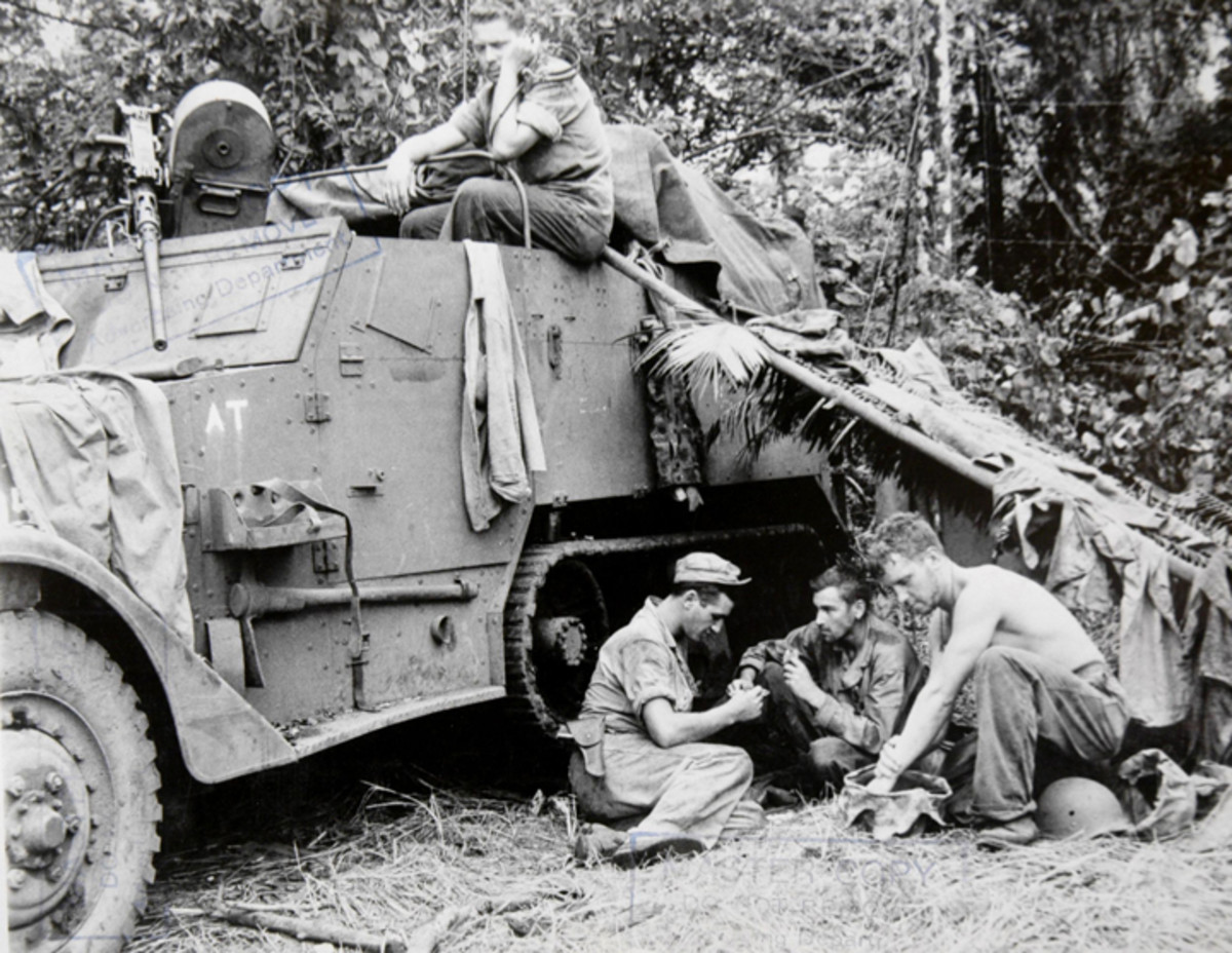 This M2 crew rests in a shelter made from palm leaves as another crewman listens to the radio headset.