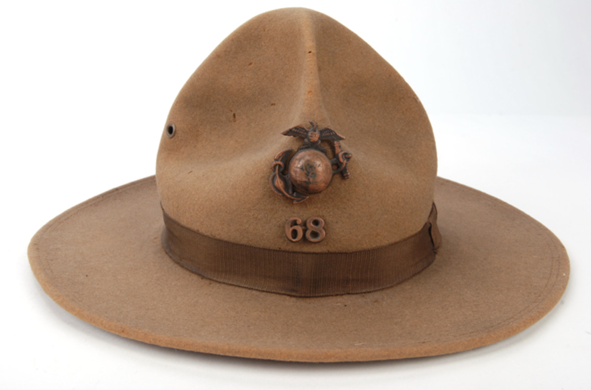 "Dark khaki fur felt P1912 crown with bronze EGA device and ""68"" metal company numerals below. During WWI, 68th Company was assigned to the U.S. Naval Station at Guantanamo Bay, Cuba."