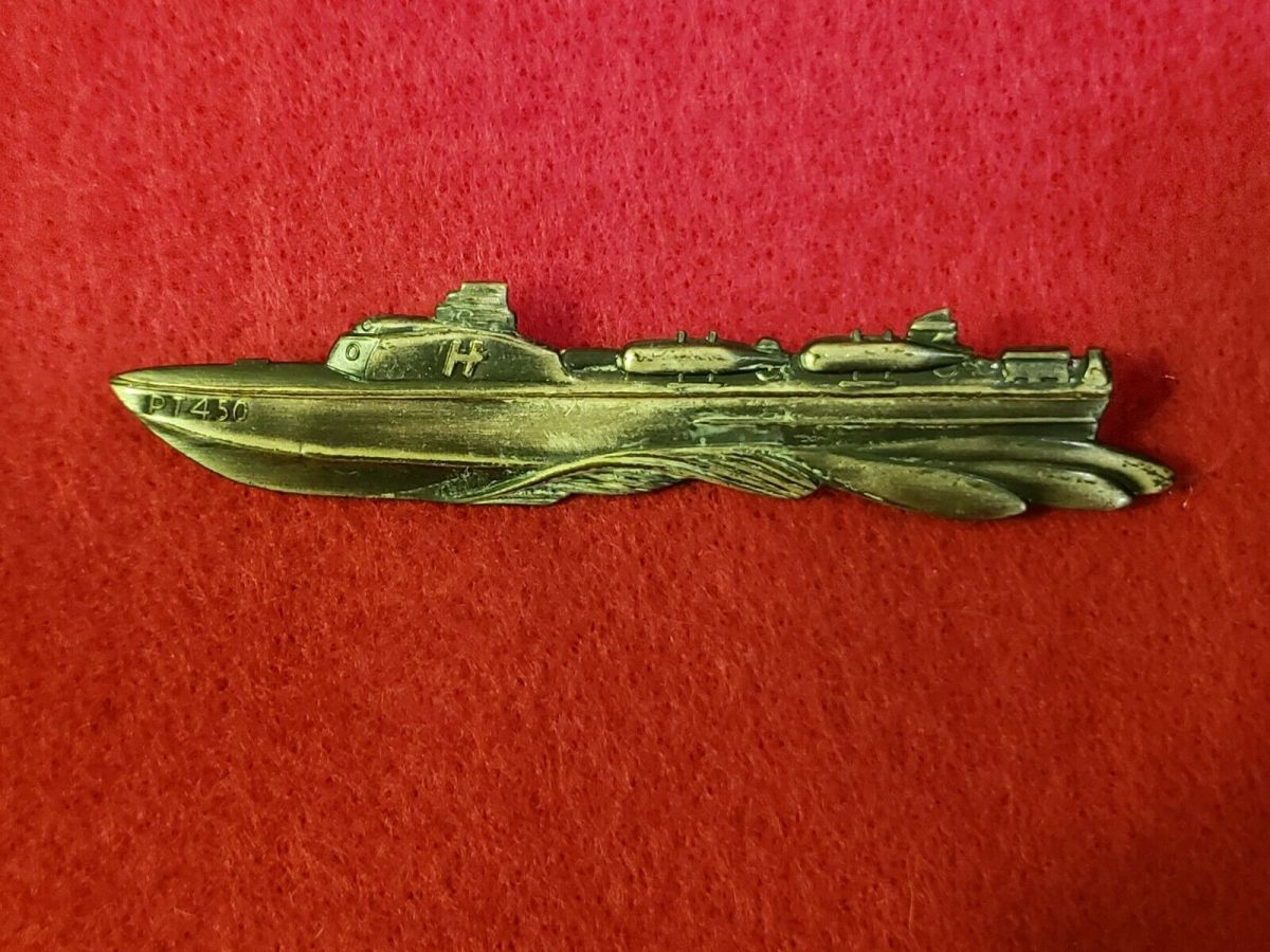 "The badge is 2-5/8"" long by 5/16"" high and depicts the side view of a PT boat throwing a bow wave. The bow of the PT boat pin is marked ""PT 450."""