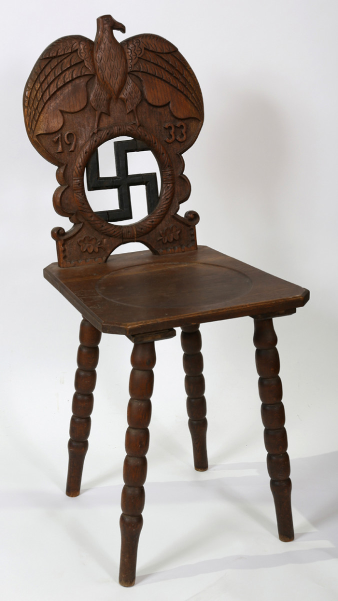 This chair, once owned by Adolf Hitler, is an excellent example of a wooden peasants' chair, embellished with an eagle, swastika and the 1933 date of Hitler's rise to power.