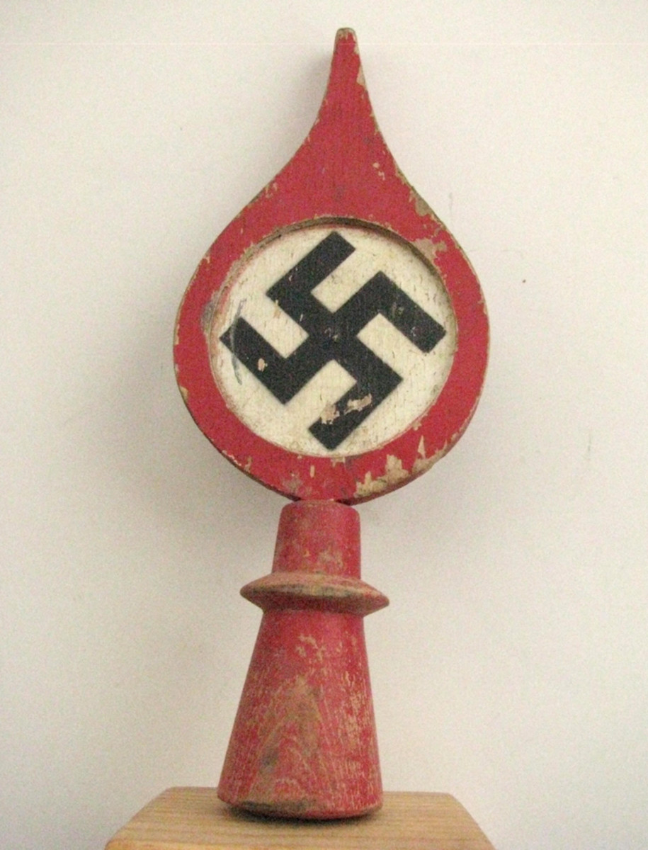 A wooden flagpole finial which was machine cut, then painted with the national colors.