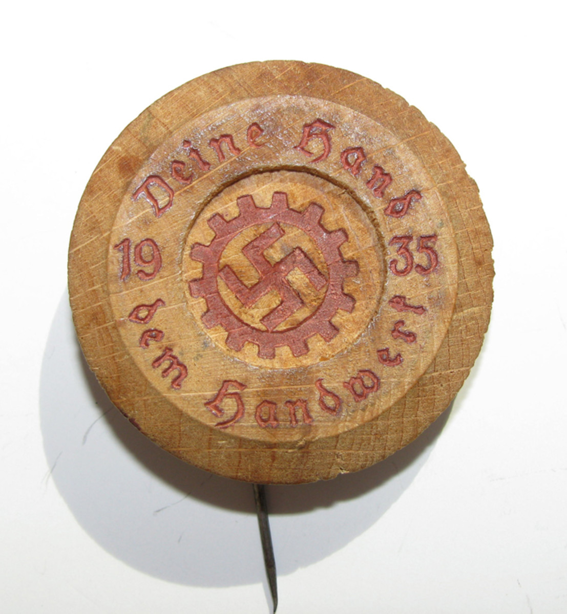 """A small Deutscher Arbeitsfront (DAF)""""tinnie"""" made from stamped and painted wood with a metal pin back."""