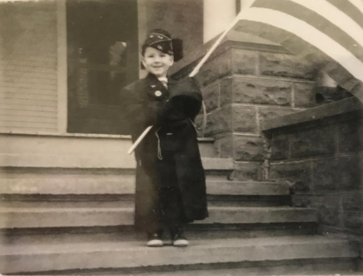 4-year-old John Adams-Graf wearing Milton Graf's American Legion cap and jacket holding a flag.