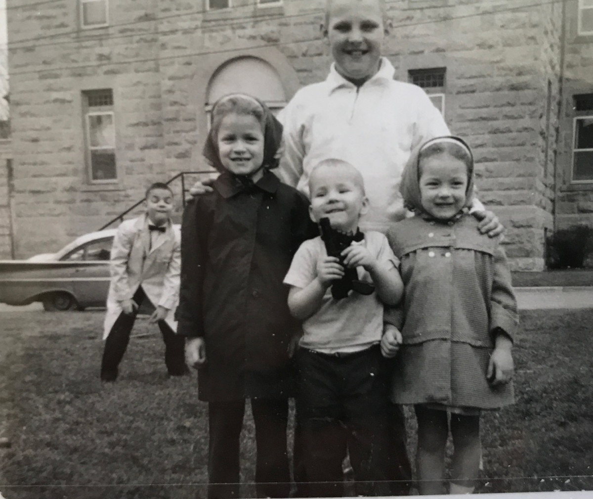 ca. 1966 photo of John Adams-Graf holding toy gun. Brothers Joe and Jim in the background.