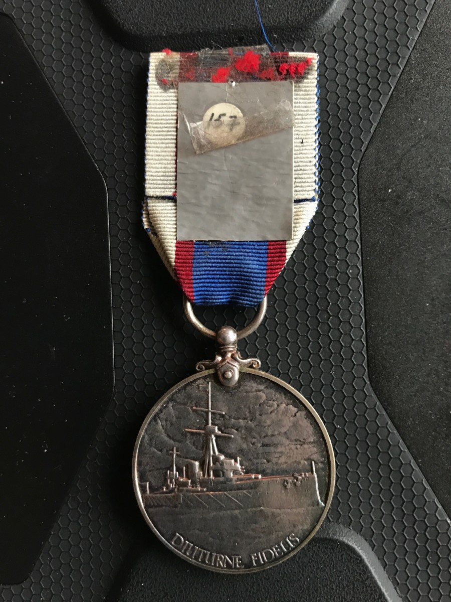 "Photo of  Fleet Reserve Long Service Medal showing a ""layer of errors"" including duct tape to hold the ribbon down, an identification on that with scotch tape over it to hold it secure."