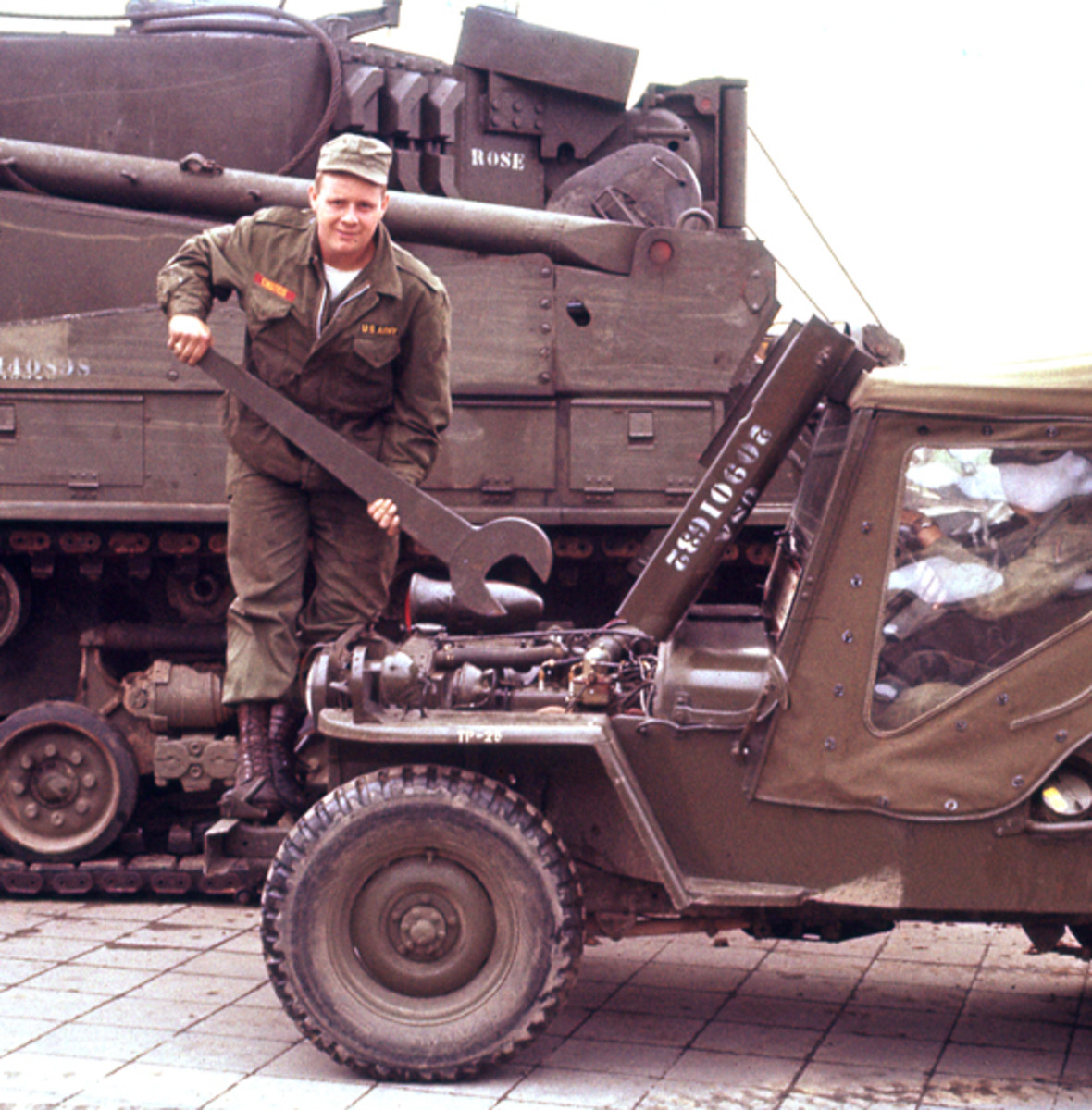 Ca. 1955 photo of Verne Kindschi standing over M38 jeep with a tank wrench