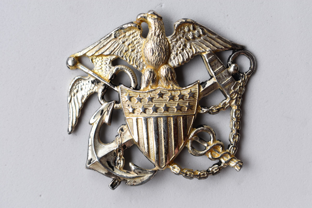 his Commissioned Corps' cap badge was made by the Blackington Company. It is the style worn by officers in the Army or Navy during WWII.