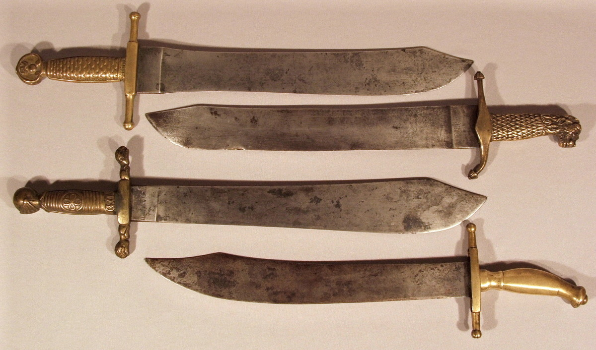 A selection of Modelo 1843 and related machetes, a family portrait of sorts. From top to bottom: The Artillery and Engineers pattern, the Infantry pattern for the Gastadores, the Modelo 1859 machete of the Civil Guard and the Machete Tagalo issued in the Philippines. Note the broad, clip-point single-edged blades made without a fuller. This is the distinguishing feature of this series of side arms.