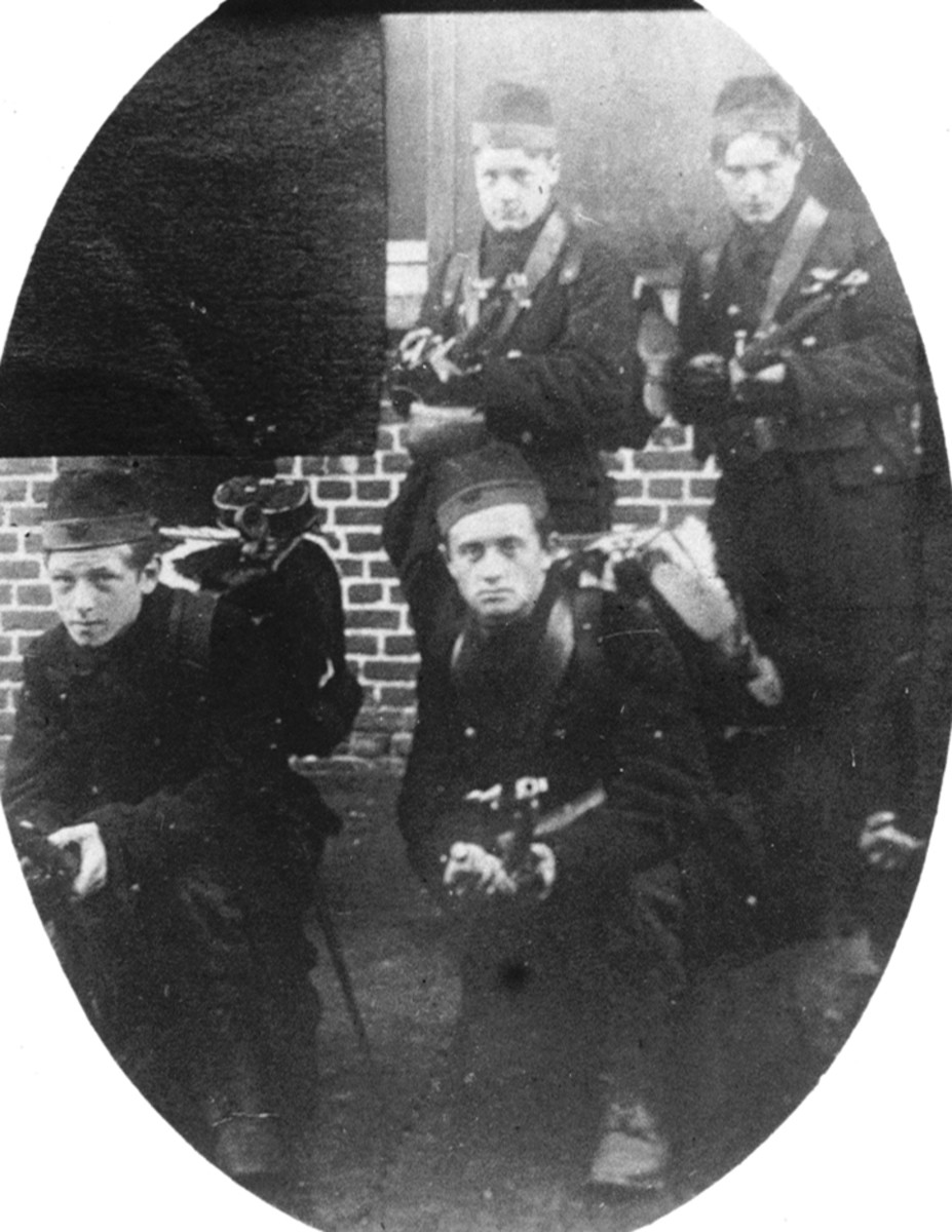 Figure 2. Made somewhat mysterious because one of the faces was covered, the original photo was probably taken in September/October 1914. It shows Belgian volunteers armed with Model 1874 French Gras rifles and bayonets. Each soldier is wearing a carabineer cap.