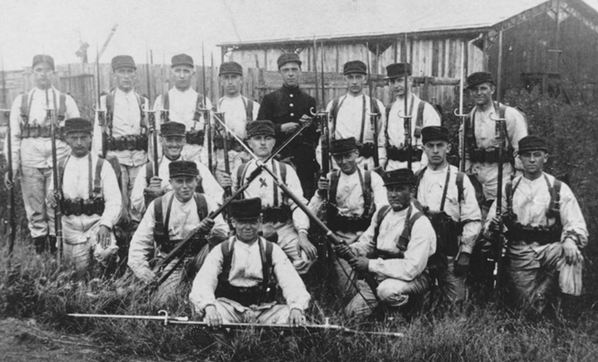 """Figure 6. A real photo postcard dated March 12, 1918, posted by the person marked with the """"X."""" He wrote on the back of the picture that it was taken at the camp of Auvours during his basic training. With the exception of the instructor, the 16 soldiers are equipped with the Model 1874 French Gras rifles and bayonets."""