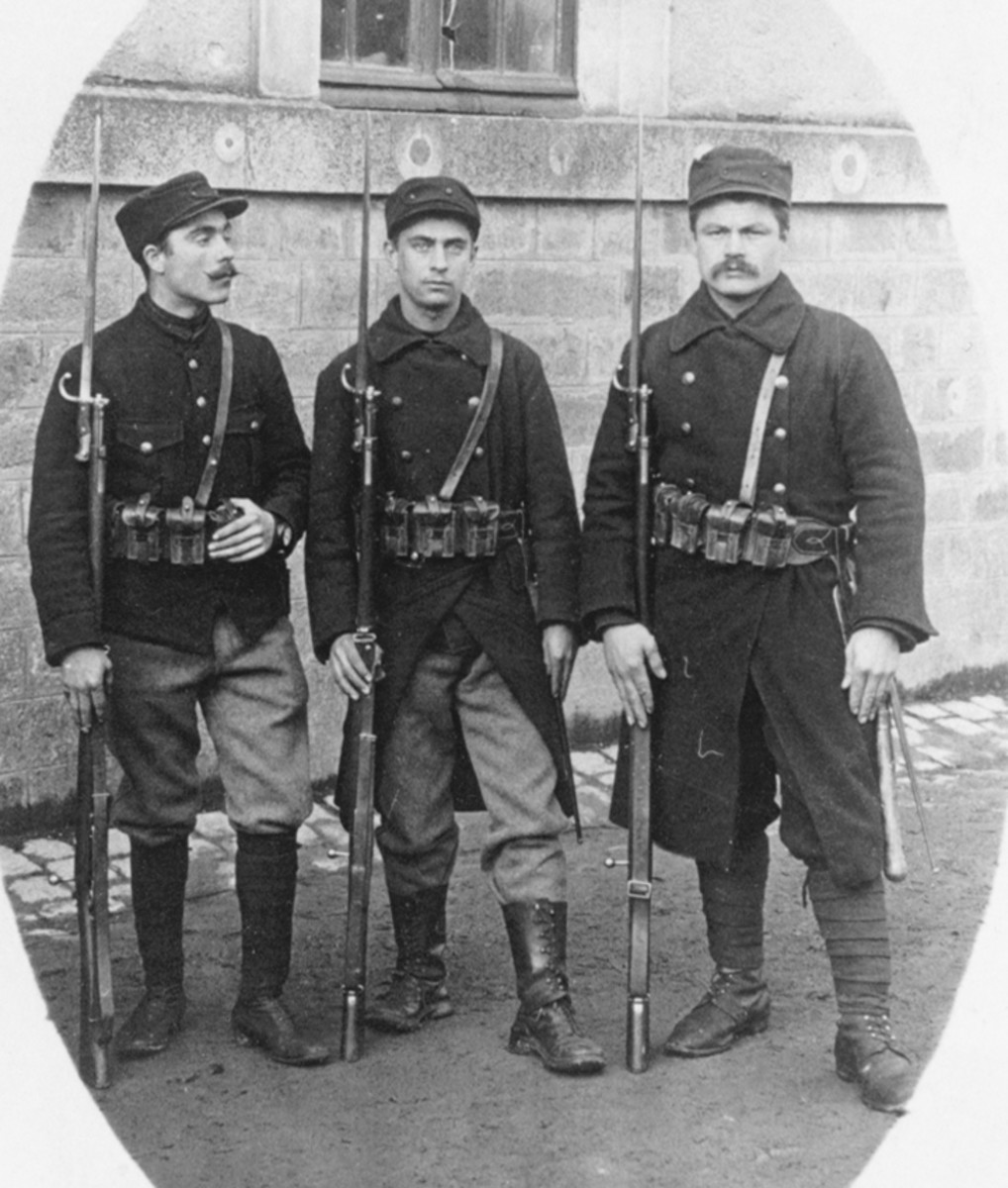 Figure 7. These three Belgian soldiers, who are wearing the transitional dark colored uniform (issued in 1915 before the introduction of the khaki colored uniform) are armed with the modified Model 1889 Mauser rifles with the Belgian Model 1874/89 Gras bayonet affixed..