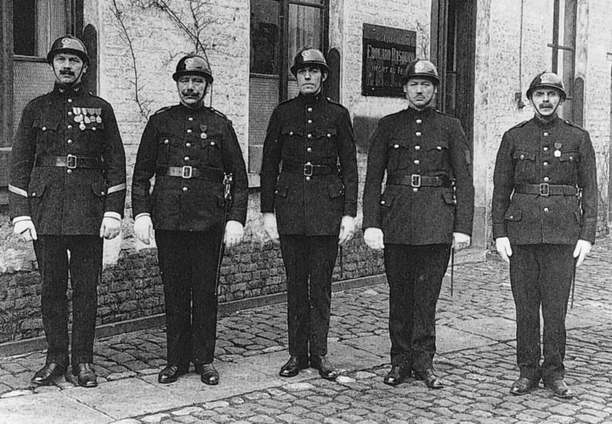 """This post-WWI real photo postcard shows firemen of the Belgian city of Sint-Jans-Molenbeek in """"full dress."""" Each of the firemen is carrying a Model 1889 Mauser yataghan in a multi-functional bayonet belt frog."""