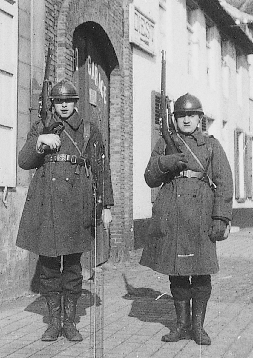 Two soldiers who are on guard duty in a street. Both of them carry a Model 1874 Gras rifle. The sign on the house above the soldier on the right indicates that the town of Diest is down the road.