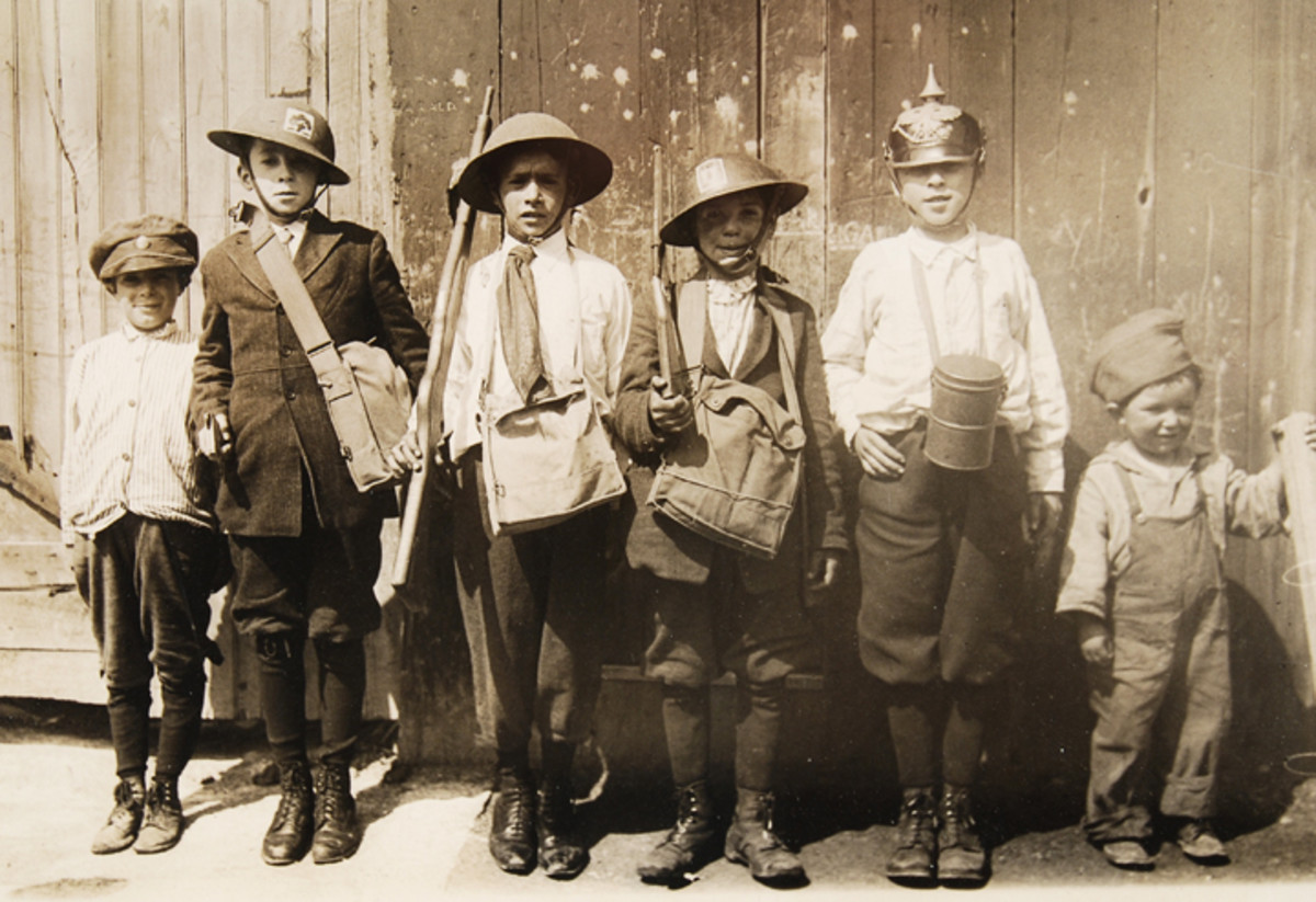 "Kids playing ""army"" wearing a variety of World War one souvenirs including helmets, gas masks, and a German Pickelhaube."