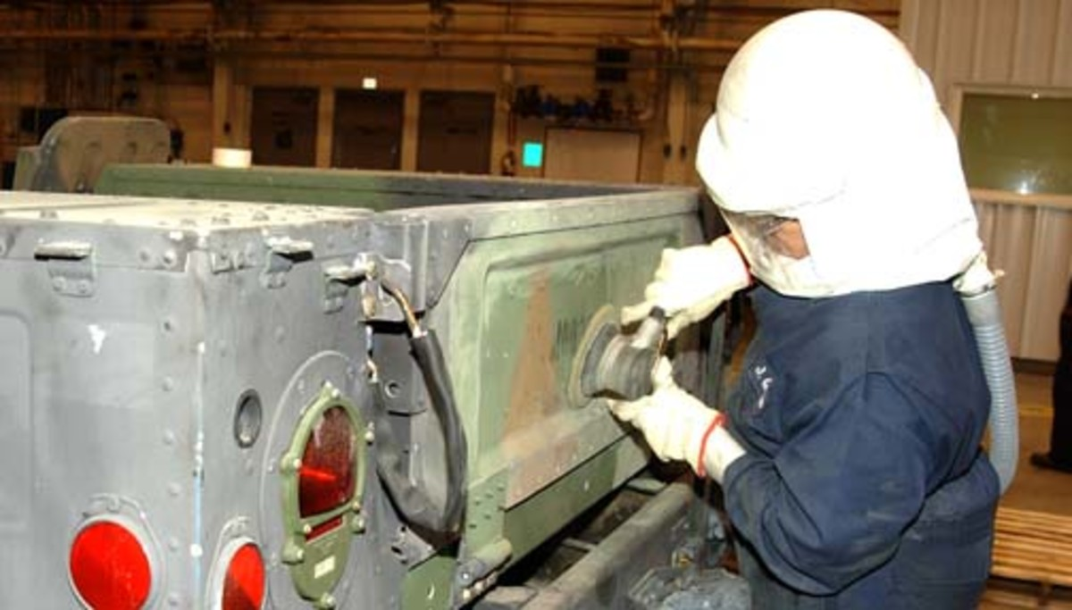 Photo from February 2007 shows a worker using a power sander to prepare a HMMWV for a new Desert Tan paint job,