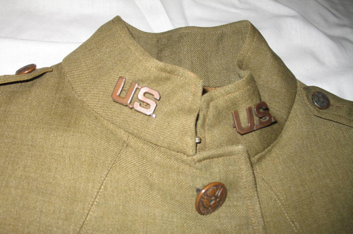 """Two high quality bronzed """"U.S."""" pin-back insignia were affixed to the tunic's collars and match the """"U.S."""" insignia on Father LeMay's overseas cap. The collars show evidence of pin-back Chaplain's insignia that were removed at some point in the tunic's history."""