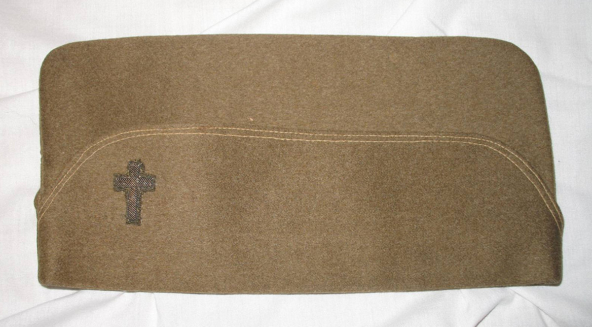 The French-made overseas cap of Chaplain LeMay features a fabric-mounted, embroidered chaplain's cross. The cap is lined in red silk and has LeMay's named penned inside.